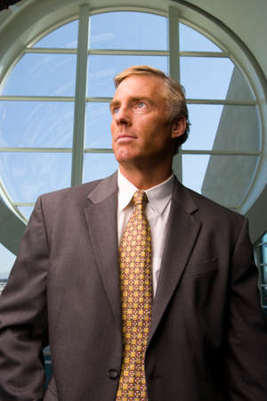 round window: Businessman standing in front of round window LANG_EVOIMAGES