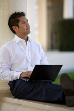 toiling: Businessman using laptop outdoors
