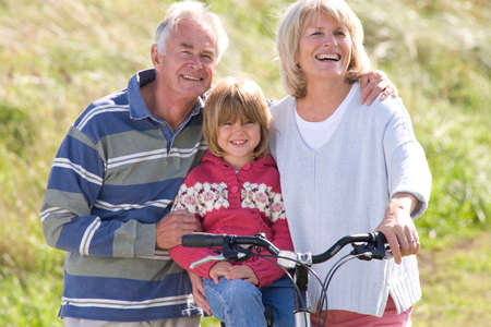 granddaughter: Grandparents with granddaughter sitting on bicycle