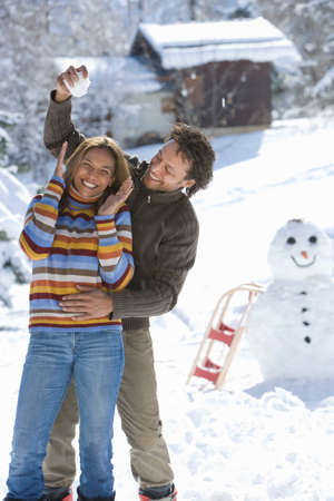 mixed race couple: Mixed race couple playing in snow with snowball