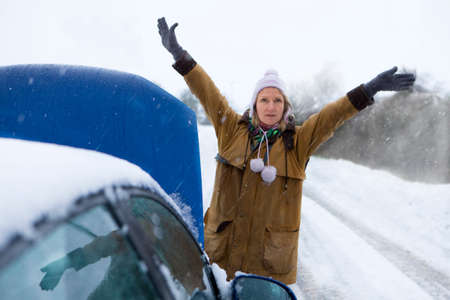 flagging: Stranded woman flagging down car in snow
