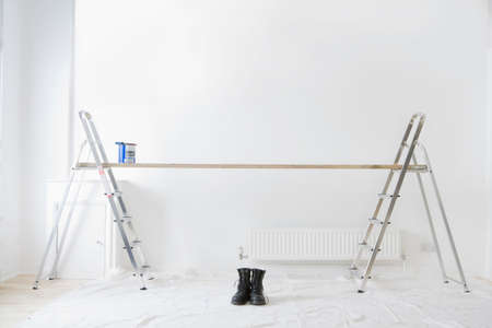 work boots: Ladders, wood plank, paint can and work boots in living room