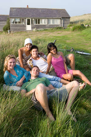 front house: Portrait of young adults sitting in front of house