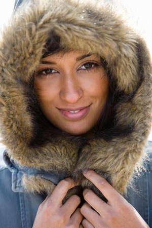 woman in fur coat: Portrait of young Asian woman in hooded fur coat