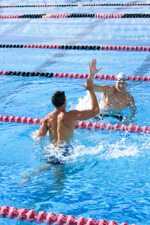 vertical divider: Two young male swimmers giving high-fives in swimming pool LANG_EVOIMAGES