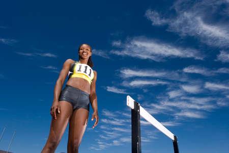 hurdle: African female athlete standing near hurdle
