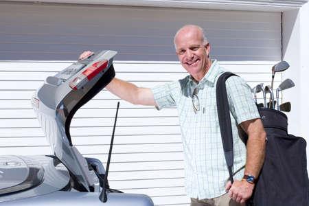 car trunk: Man loading golf clubs into car trunk