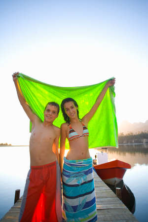 girl posing: Teenagers holding towel on dock LANG_EVOIMAGES