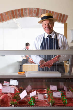 meat counter: Butcher in uniform behind meat counter