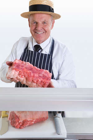 meat counter: Butcher in uniform holding roast behind meat counter LANG_EVOIMAGES