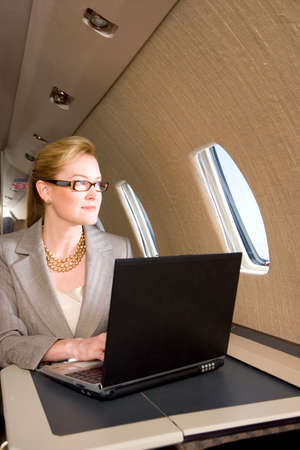 one mid adult woman only: Businesswoman with laptop computer on aeroplane, looking out window