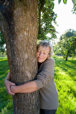 conservationist: Mature woman embracing tree, eyes closed LANG_EVOIMAGES