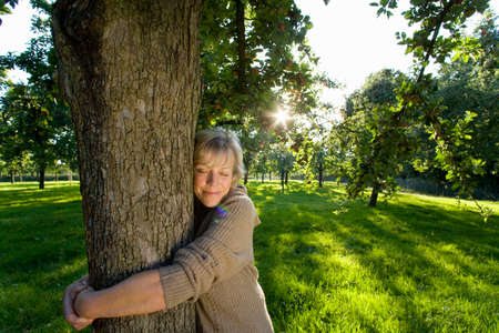 conservationist: Mature woman embracing tree, eyes closed (lens flare) LANG_EVOIMAGES