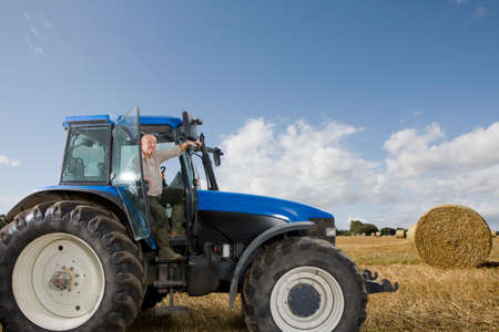 hay field: Farmer stepping down from tractor in hay field