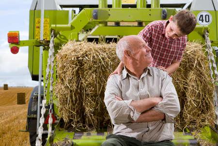 Farmer und Enkel auf Traktor mit Stroh