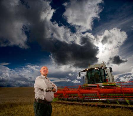 cosechadora: Granjero que se coloca al lado de la cosechadora en campo de trigo LANG_EVOIMAGES