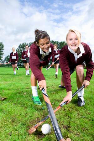 hockey sobre cesped: Retrato de adolescentes sonrientes que juegan hockey sobre c�sped LANG_EVOIMAGES