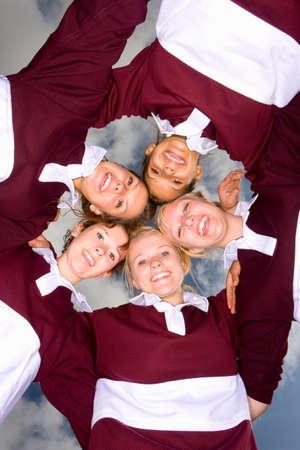 directly below: Portrait of smiling teenage girls hugging in sports uniforms