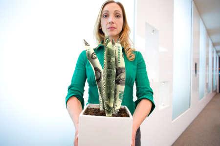 financial reward: Portrait of businesswoman holding plant made from dollar bills LANG_EVOIMAGES