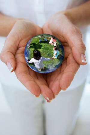 idealism: Close up of womans hands cupping crystal ball globe with children