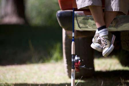 Fishing pole: Boys feet next to fishing pole