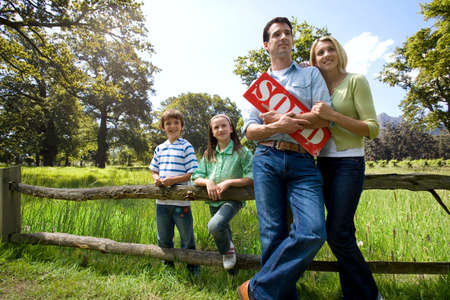 sold sign: Family leaning on rural fence and holding sold sign LANG_EVOIMAGES