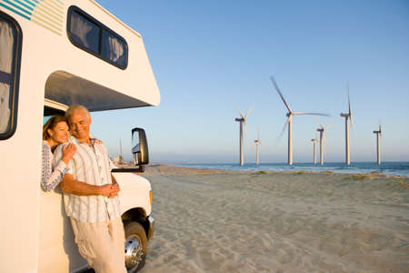 motor home: Couple hugging by motor home with wind turbines in distance