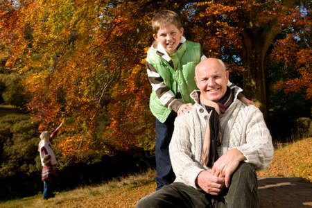 tetbury: Portrait of grandfather and grandson in woods with autumn leaves