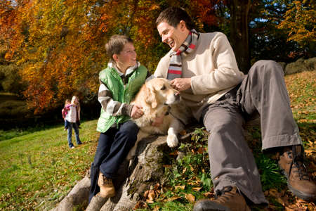 tetbury: Father, son, and dog sitting on tree stump in woods
