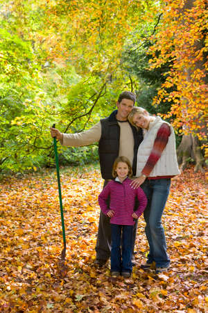 tetbury: Portrait of family with rake standing in autumn leaves