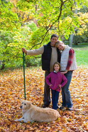 tetbury: Portrait of family and dog with rake standing in autumn leaves