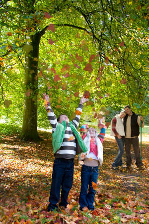 tetbury: Boy and girl throwing autumn leaves in air