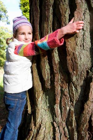 idealism: Girl hugging tree trunk LANG_EVOIMAGES