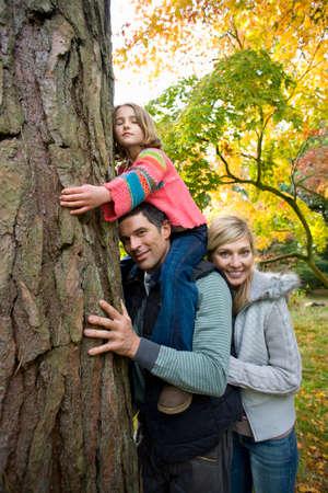 idealism: Portrait of family hugging tree trunk LANG_EVOIMAGES