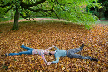 tetbury: Couple holding hands and laying in autumn leaves LANG_EVOIMAGES