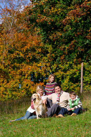 tetbury: Portrait of family and dog sitting in grass