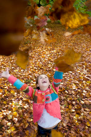 tetbury: Girl throwing autumn leaves in air LANG_EVOIMAGES
