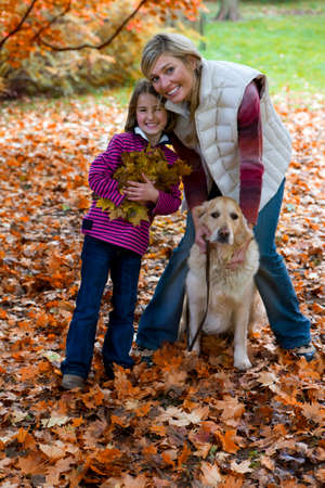 tetbury: Mother, daughter, and dog standing in autumn leaves LANG_EVOIMAGES