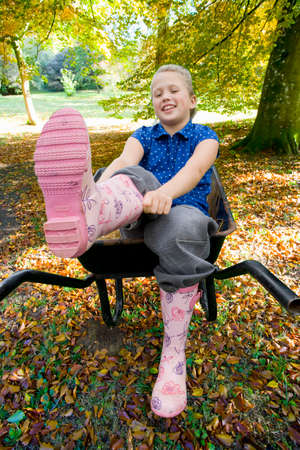 putting on: Girl sitting in wheelbarrow and putting on rubber boots