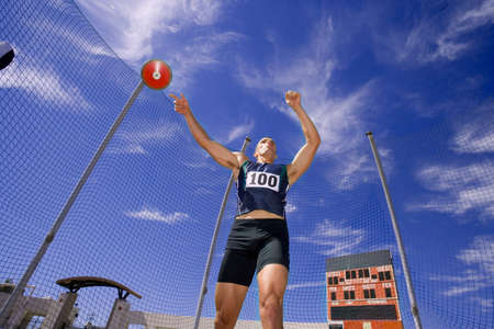 discus: Male athlete throwing discus, low angle view