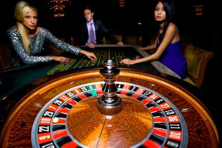ruleta de casino: Hombre flanqueado por las mujeres, los juegos de azar en la mesa de la ruleta, retrato