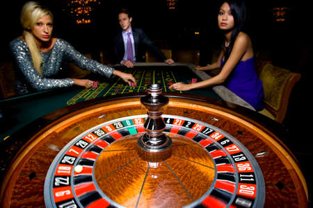 roulette wheel: Man flanked by women, gambling at roulette table, portrait