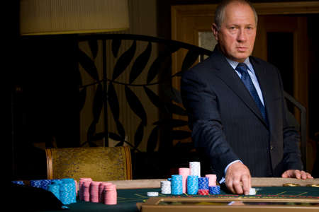 high stakes: Mature man gambling, hand on chips, portrait