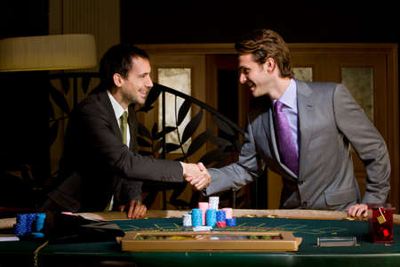 high stakes: Two young men shaking hands over poker table, smiling, side view LANG_EVOIMAGES