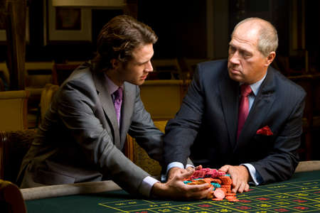 roulette table: Mature man giving young man pile of gambling chips at roulette table
