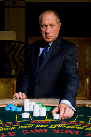 Mature man placing gambling chips on poker table, portrait