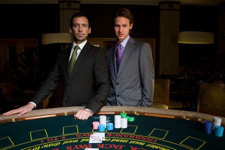 high stakes: Two young men gambling at poker table, smiling, portrait LANG_EVOIMAGES