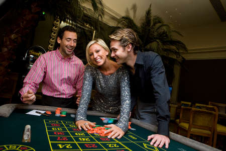 roulette table: Young woman and friends gambling at roulette table, hands on chips, smiling, portrait