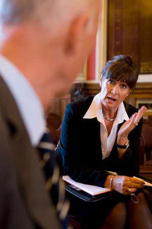 registrar: Female registrar on chair in conversation with man LANG_EVOIMAGES