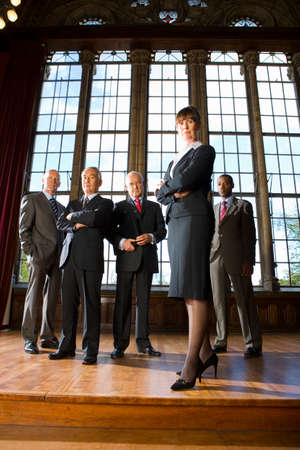 professionalism: Businesswoman with arms crossed by businessmen in hall, portrait, low angle view